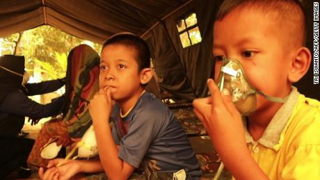 Children get a dose of oxygen from a Red Cross volunteer at a village in Jambi on September 24, 2019.