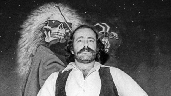 Robert Hunter poses in front of a Blues For Allah backdrop at the Grateful Dead's rehearsal studio, Club Front, in November 1977 in California.