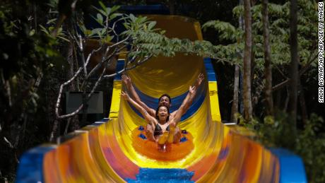Theme park patrons slide down on a floater on the world's longest water slide at Escape theme park in Teluk Bahang, Malaysia on September 25, 2019. - One of the world's longest water slides was unveiled in Malaysia on September 25, a kilometre-long chute that starts from a hilltop before twisting and turning through dense jungle and splashing into a pool. (Photo by SADIQ ASYRAF / AFP)        (Photo credit should read SADIQ ASYRAF/AFP/Getty Images)