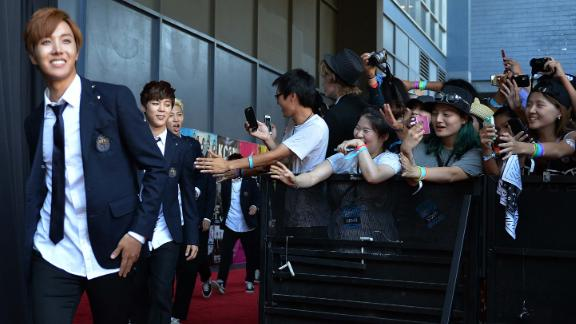 Members of Korean K-pop group BTS arrive on the red carpet during the K-CON 2014 at the Los Angeles Memorial Sports Arena on August 10, 2014.