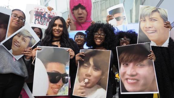 Fans of the Korean boy band group BTS pose with photos of their idols outside the 2017 American Music Awards, November 19, 2017 in Los Angeles, California.