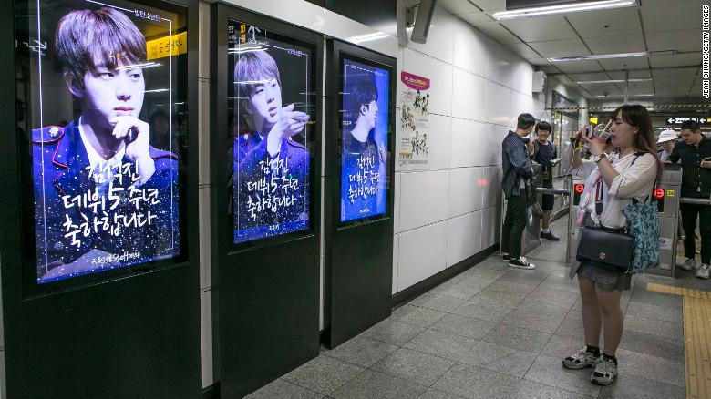 A fan takes pictures of photos of BTS singer Jin which are displayed at Hongdae Subway Station on June 2, 2018 in Seoul, South Korea. Fans bought the advertising space to celebrate Jin's 5th anniversary of his debut with BTS.