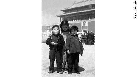 4-year-old Xiao Ji Anwen and his older sister standing with a girl in a neighborhood in Tiananan Square in 1953.
