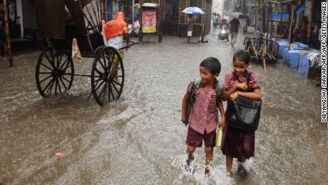 Indian schoolchildren walk through a flooded road during heavy rain in Kolkata on September 25, 2019.