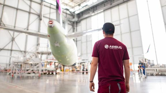14 June 2018, Hamburg, Germany: An Airbus employee stands in front of a plane in the new A 320 production line on the premises of Airbus-Finkenwerder. Photo: Daniel Reinhardt/dpa (Photo by Daniel Reinhardt/picture alliance via Getty Images)