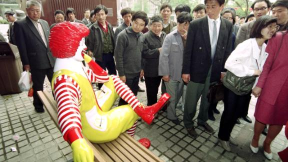 Passers-by keep their distance from Ronald McDonald as he sits outside the first McDonalds restaurant to be opened in Beijing on April 20, 1992.
