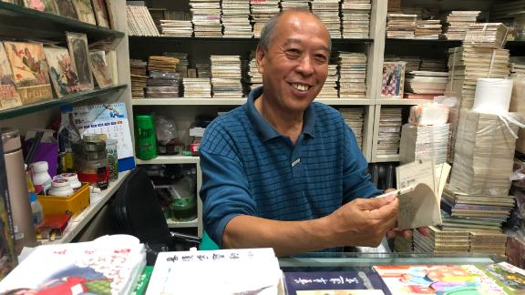 """Ma sitting in his """"lianhuanhua"""" comic book store in Beijing in September, surrounded by his life's work."""