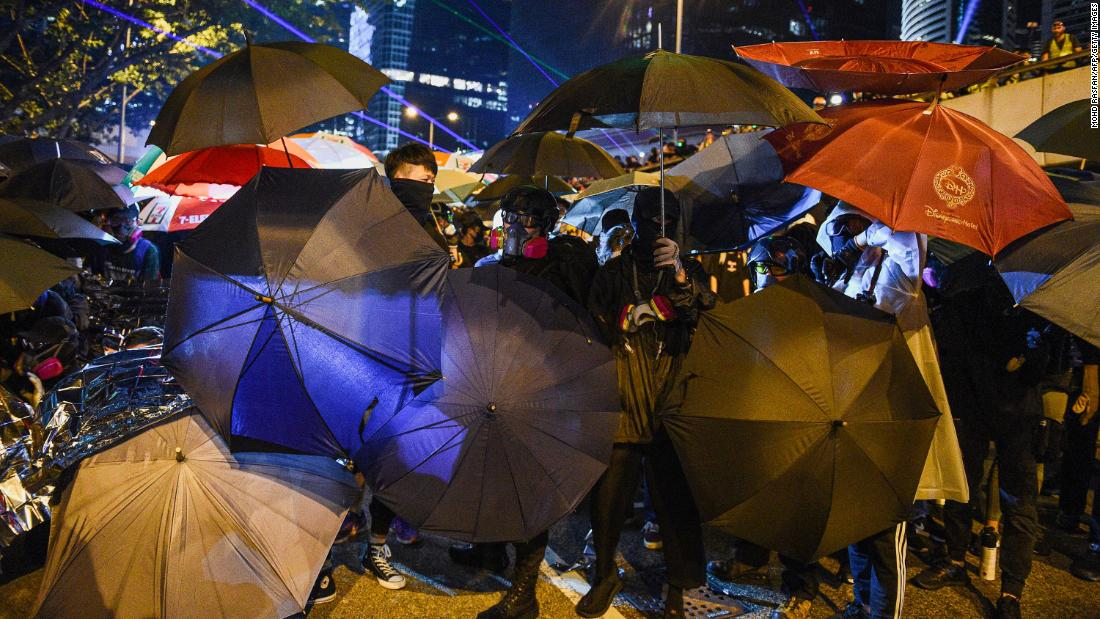 Protesters protect themselves after a group occupied a main road near the central government offices in Hong Kong on Saturday, September 28.