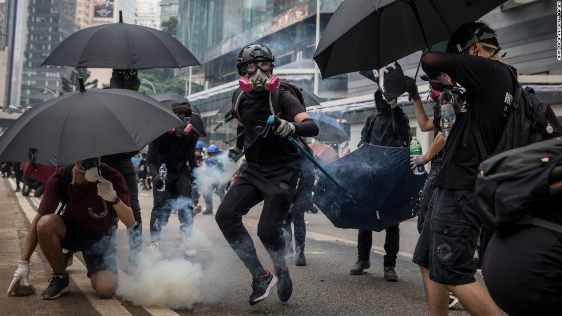 A pro-democracy protester throws a tear gas canister back at police on September 29.