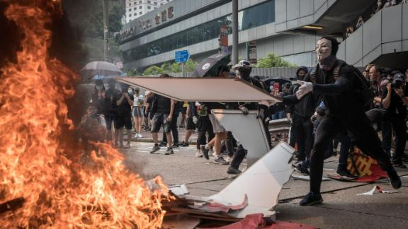 A pro-democracy protester burns a banner during a march in Hong Kong.
