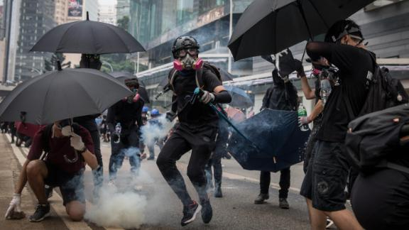 A pro-democracy protester throws a tear gas canister back at police amid clashes on Sunday.