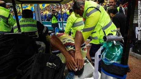 Giovani Dos Santos of America is taken out the field while he is crying after being injured during the 12th round match between America and Chivas.