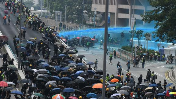 Hong Kong police fire a water cannon toward protesters gathered outside the central government offices after taking part in an unsanctioned march through Hong Kong on September 29.