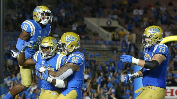 PASADENA, CA - OCTOBER 20: (L-R) Demetric Felton #10, Joshua Kelley #27, Devin Asiasi #86 and Jake Burton #73 of the UCLA Bruins celebrate Kelley's rushing touchdown during the second half of the NCAA college football game against the Arizona Wildcats at the Rose Bowl on October 20, 2018 in Pasadena, California. The Bruins defeated the Wildcats 31-30. (Photo by Victor Decolongon/Getty Images)