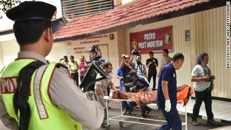 Indonesian police and forensic officials shift the body of a Canadian citizen who was killed during the January 14, 2016 terrorist attacks in Jakarta. The weapons used during the attack were funded by Adi Jihadi, who had taken a radicalized domestic worker from Hong Kong as his second wife.