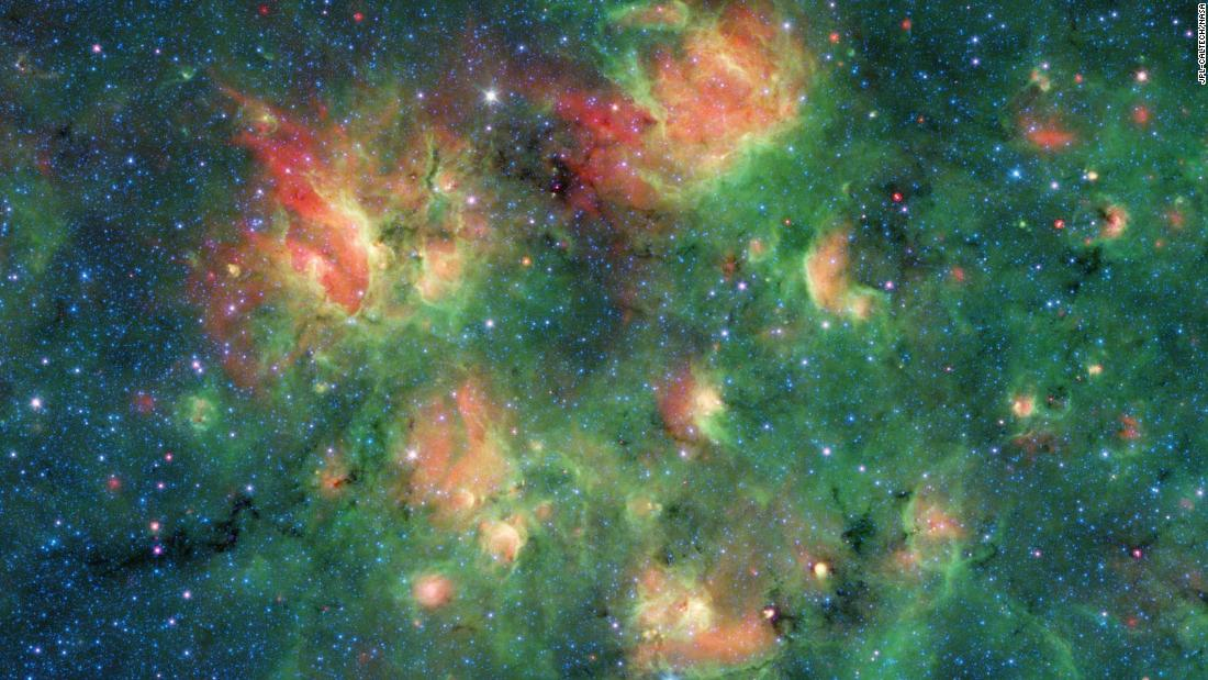 This infrared image from Spitzer shows a cloud of gas and dust full of bubbles, which are inflated by wind and radiation from massive young stars. Each bubble is filled with hundreds to thousands of stars, which form from dense clouds of gas and dust.