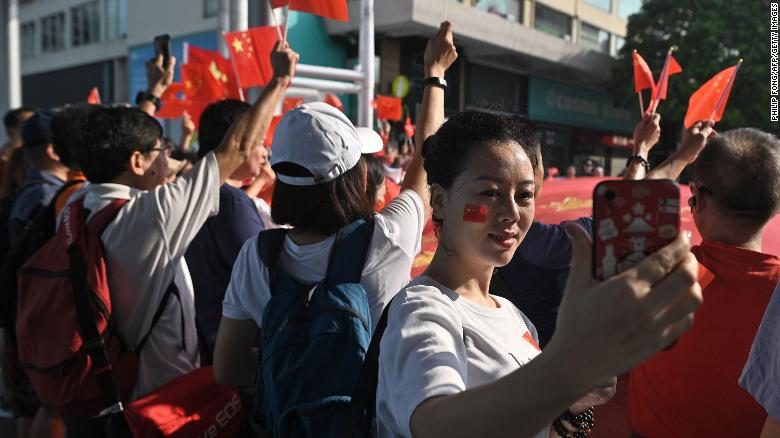 A woman takes a selfie during a pro-Beijing flash mob rally in the Tsim Sha Tsui district in Hong Kong on October 1, 2019, to mark the 70th anniversary of communist China's founding.
