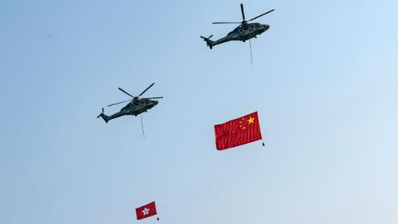 Helicopters fly the flags of China and Hong Kong over Victoria Harbour during a flag-raising ceremony at Golden Bauhinia Square in Hong Kong.