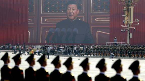 A screen shows Chinese President Xi Jinping delivering a speech at the start of the parade in Beijing.