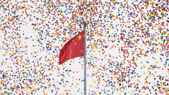 Balloons fly past a national flag at the end of a military parade at Tiananmen Square in Beijing.