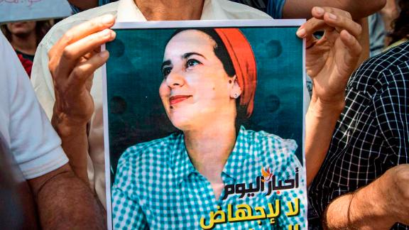 """A demonstrator holds up a sign showing the portrait of Hajar Raissouni, a Morrocan journalist of the daily newspaper Akhbar El-Youm, with a caption below in Arabic and English reading """"Akhbar El-Youm: no to the abortion of the free press"""", during a protest outside a courthouse holding her trial on charges of abortion in the capital Rabat on September 9, 2019. (Photo by FADEL SENNA / AFP)        (Photo credit should read FADEL SENNA/AFP/Getty Images)"""