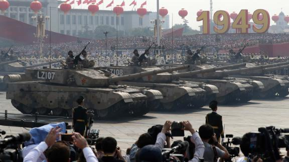 Army vehicles parade as members of a Chinese military honor guard march during the 70th anniversary celebrations in Beijing.