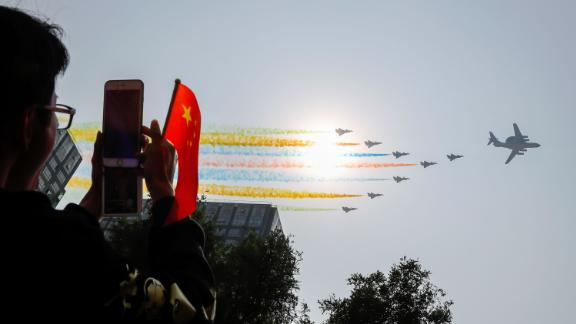 An onlooker photographs the Chinese military planes as they trail colored smoke during the celebrations.