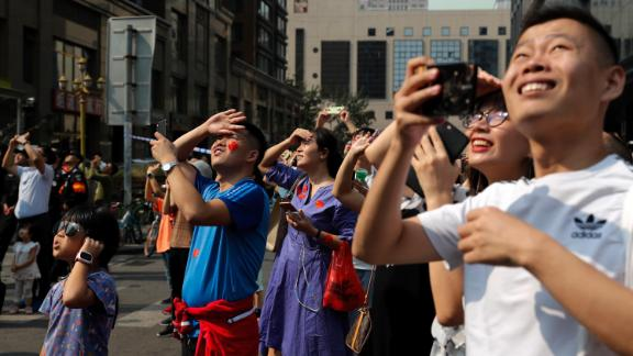 Residents watch Chinese military planes fly in formation above the capital city.