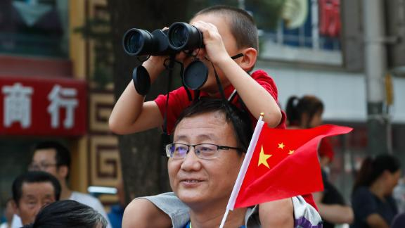 A child uses binoculars to watch the floats in the anniversary parade.