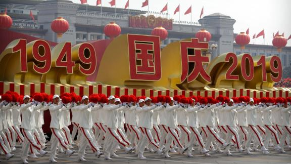 Participants wave flowers as they march next to a float commemorating the 70th anniversary of the founding of Communist China.