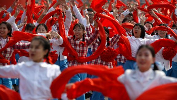 Participants wave red cloth during the National Day parade in Beijing.
