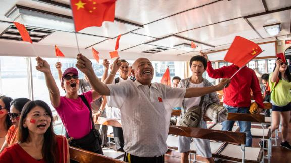 Pro-Beijing supporters wave Chinese flags on the Star Ferry in Hong Kong.