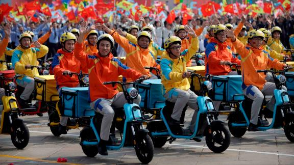 Participants dressed as deliverymen wave during the parade,