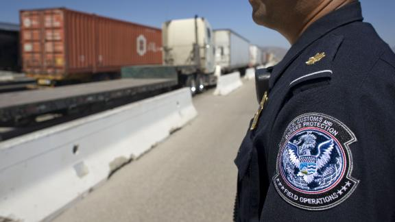 A U.S. Customs and Border Protection (CBP) officer stands next to a line of trucks entering from Mexico at the Otay Mesa Cargo Port of Entry in San Diego, California, U.S., on May 23, 2017. The skirmish among House Ways and Means Committee Republicans over a border tax provision resurfaced during a May 24 hearing where Treasury Secretary Steven Mnuchin was testifying on the president
