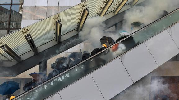 Protesters react after police fired tear gas near the central government offices in Hong Kong