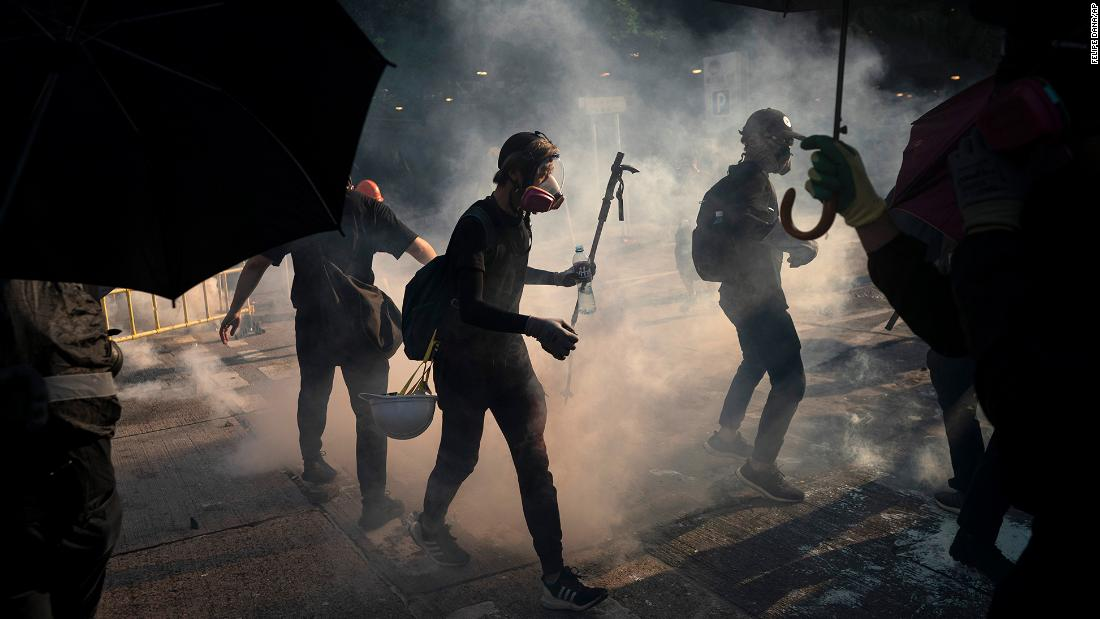 Protesters stand surrounded by smoke from tear gas shells on October 1.
