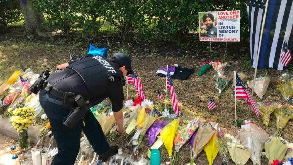 A law enforcement officer visits a makeshift memorial set up for Deputy Sandeep Dhaliwal.
