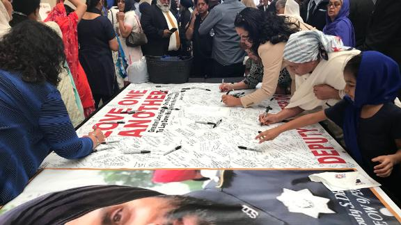 Mourners sign a banner dedicated to Dhaliwal on Wednesday, in the arena where his funeral is being held.