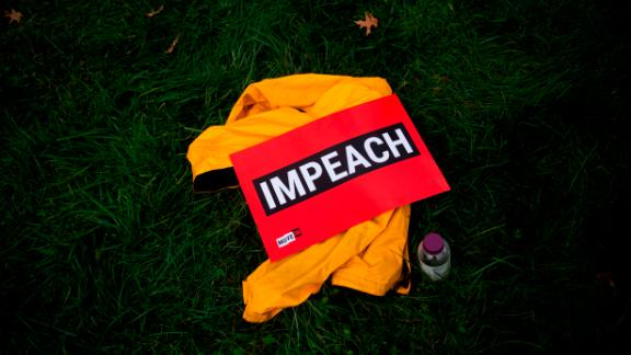 """A sign reading """"impeach"""" is seen on the grass during the """"People"""