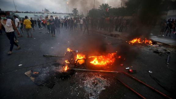 Iraqi protesters stand next to burning tyres during a demonstration in Baghdad on October 2, 2019.