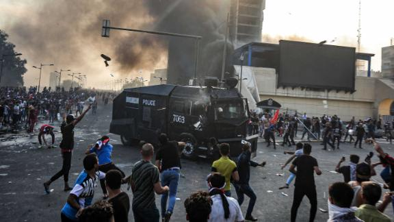Protesters clash with an Iraqi riot police vehicle during a demonstration against state corruption and poor services, between the capital Baghdad