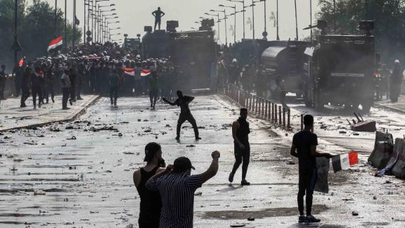Protesters clash with riot police vehicles in the Iraqi capital on October 1.