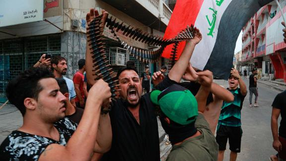 Protesters hold bullets they say belonged to Iraqi police during a protest in Baghdad on Tuesday.