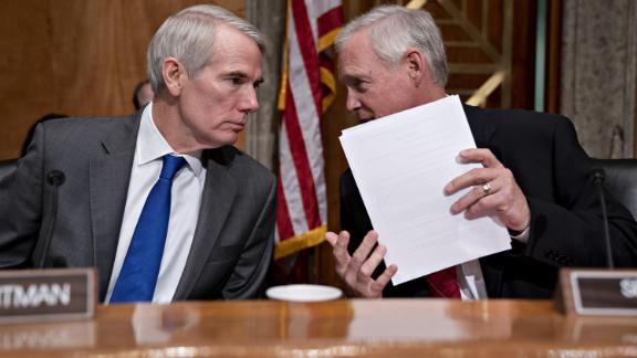 Senator Ron Johnson, a Republican from Wisconsin and chairman of the Senate Finance Committee, right, talks to Senator Rob Portman, a Republican from Ohio, during a hearing on migration at the United States southern border in Washington, DC on July 30, 2019.