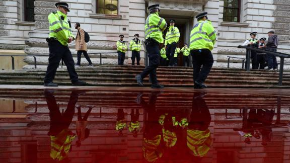 Police officers stand next to a pool of fake blood outside Britain's finance ministry.