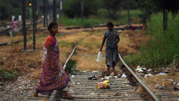Women walking on train tracks in an area where people defecate in the open near Nizamuddin railway station in New Delhi on September 27, 2019.