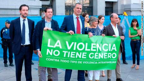 "Vox spokesman Javier Ortega Smith (center) takes part in a minute's silence for a victim of gender-based violence with a banner that reads: ""Violence has no gender. Against all types of domestic violence."""