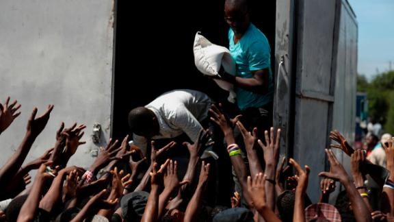 People in need of food call out for a sack of rice during a federal government distribution of food and school supplies to some residents of Cite Soleil, in Port-au-Prince, Haiti, Thursday, Oct. 3, 2019. The daily struggles of Haitians have only become more acute as recent anti-government protests and roadblocks force the closure of businesses, sometimes permanently, as people lose jobs and dwindling incomes fall behind a spike in prices. (AP Photo/Rebecca Blackwell)