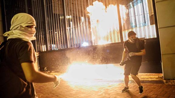 Protesters throw petrol bombs at the gate to the Tsuen Wan police station on Wednesday, October 2.