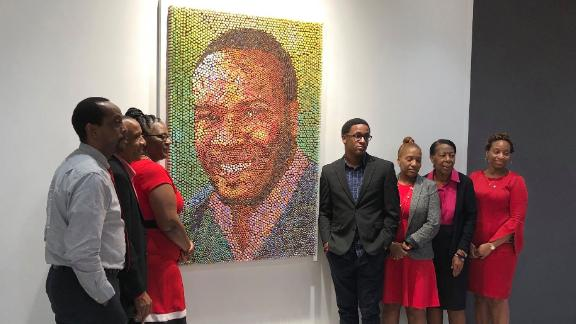 Members of Botham Jean's family pose with his portrait at PricewaterhouseCooper's Dallas office.